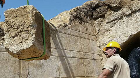 Workers using a crane remove one of the large stone blocks from a wall originally sealing the entrance. (Source: AP)