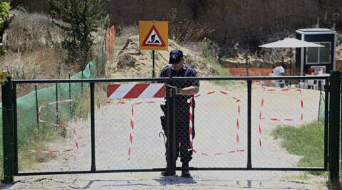 A police man locks the entrance to the site that archaeologists are excavating. (Source: AP)
