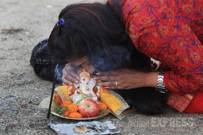 A girl whispers in Lord Ganesh's ears before immersing the idol in the sea in Mumbai. (Source: Express photo Ganesh Shirsekar)