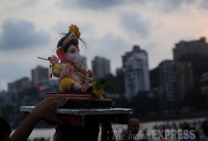 A devotee is seen carrying Ganesh idol on his head for immersion. (Source: Express photo Ganesh Shirsekar)