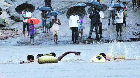 Children cling on to brass pots as they cross Hiran. Source: File Express Photo