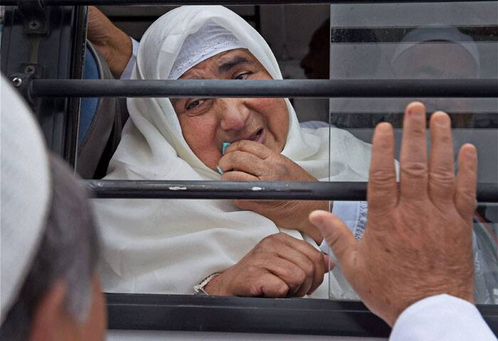 The first batch of pilgrims from Jammu and Kashmir for Haj 2014 left the summer capital of Srinagar on Wednesday on a direct flight to Madina in Saudi Arabia. <br /><br /> A relative waves  to a pilgrim leaving for airport from Haj House Bemina in Srinagar on Wednesday. The first batch of Haj pilgrims left for Jeddah from Srinagar Airport to perform annual Haj pilgrimage. (Source: PTI Photo)