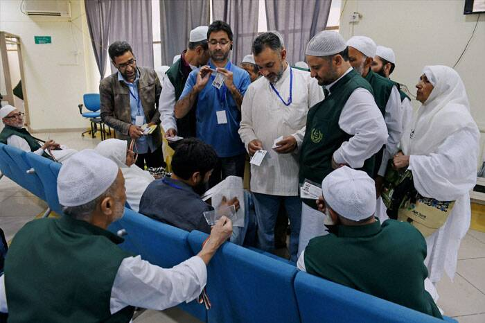 Haj pilgrims collecting documents from Haj officials at Haj House Bemina in Srinagar on Wednesday.  (Source: PTI Photo)