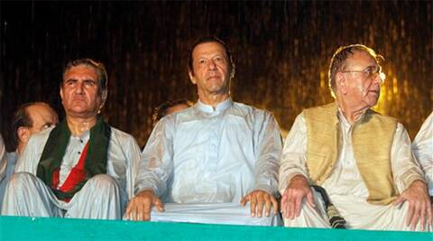 Pakistan's cricketer-turned-politician Imran Khan, center, with other his party leaders attend an anti government rally during heavy rain in Islamabad, Pakistan, Saturday. (Source: AP Photo)