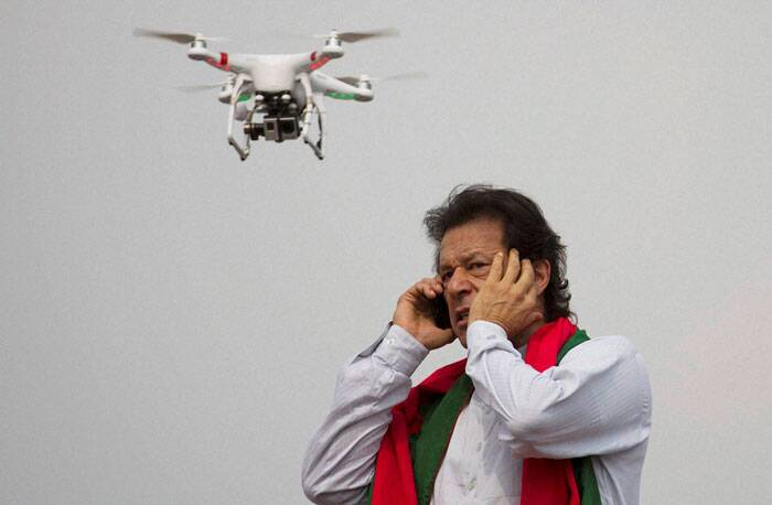 Pakistan too has been on the tenterhook through the massive civilian protests portrayed in the images, Insignia of which is the Image of a rather angry looking Imran Khan speaking on his phone while a drone keeps watch over the proceedings in Islamabad. <br /> Pakistan's cricketer-turned-politician Imran Khan talks over a phone as a camera-equipped drone hovers outside a parliament in Islamabad, Pakistan on August 21, 2014. Thousands of Khan's supporters are besieging parliament for a second day Thursday to pressure Prime Minister Nawaz Sharif to resign over alleged election fraud. (Source: AP)