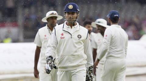 India captain MS Dhoni walks from the pitch as rain begins to fall on the second day of the fourth Test in Manchester on Friday. (Source: AP)