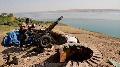 A Kurdish peshmerga fighter prepares his weapon at his combat position near the Mosul Dam at the town of Chamibarakat outside Mosul, Iraq. (Source: AP photo)