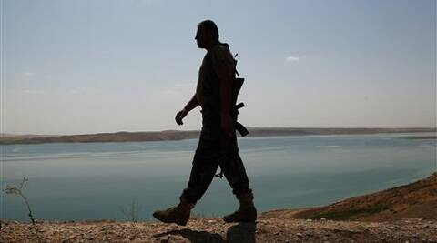 A Kurdish peshmerga fighter patrols near the Mosul Dam at the town of Chamibarakat outside Mosul, Iraq, Sunday. (Source: AP photo)
