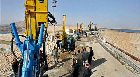 Workers operate machines at a construction site on the dam in Mosul, northwest of Baghdad, Iraq. (Source AP photo)