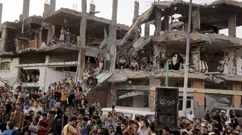 Palestinians attend a victory rally organized by masked militant of Izzedine al-Qassam Brigades, military wing of Hamas, at the debris of destroyed houses in Shijaiyah, neighborhood of Gaza City. (Source: AP)