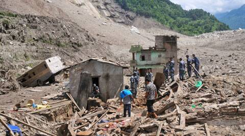 Nepalese security personnel gather for rescue work at the site of a landslide in Sindhupalchowk area, about 120 kilometers (75 miles) east of Katmandu, Nepal, Saturday, Aug. 2, 2014. A massive landslide killed at least eight people and blocked a mountain river in northern Nepal on Saturday, causing the water to form a lake that was threatening to burst and sweep several villages, officials said. (AP Photo/Dinesh Gole)