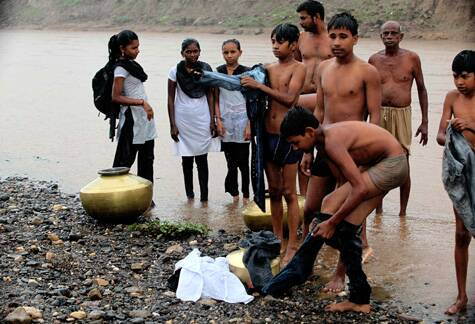 A metal pot helps students in Narmada cross the Airan river to get to school. (Source: Express photo by Bhupendra Rana)