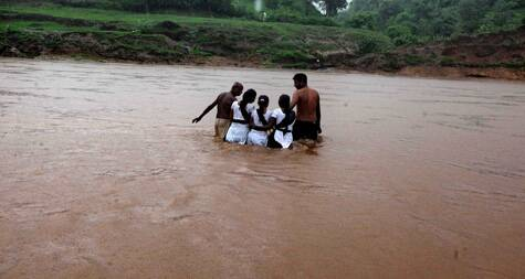 Village swimmers helps the girls cross the Airan River on a metal pot. (Source: Express photo by Bhupendra Rana)