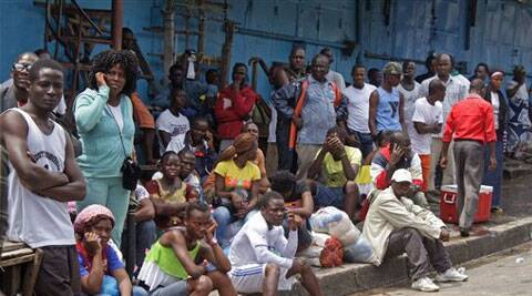 People wait for Liberian security forces to allow them to deliver foodstuff to friends and family members in the West Point area that has been hardest hit by the Ebola virus. (Source: AP)