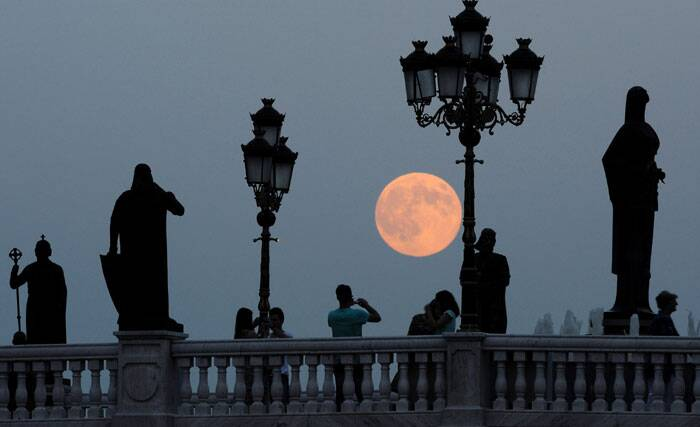 People take photos as a perigee moon also known as a supermoon rises above a bridge over Vardar River in Skopje, Macedonia. (Source: AP)