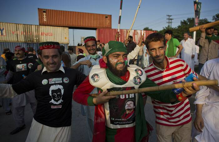 Supporters of Pakistan's cricketer-turned-politician Imran Khan dance before marching to Parliament, which authorities blocked access to with shipping containers in Islamabad. (Source: AP)