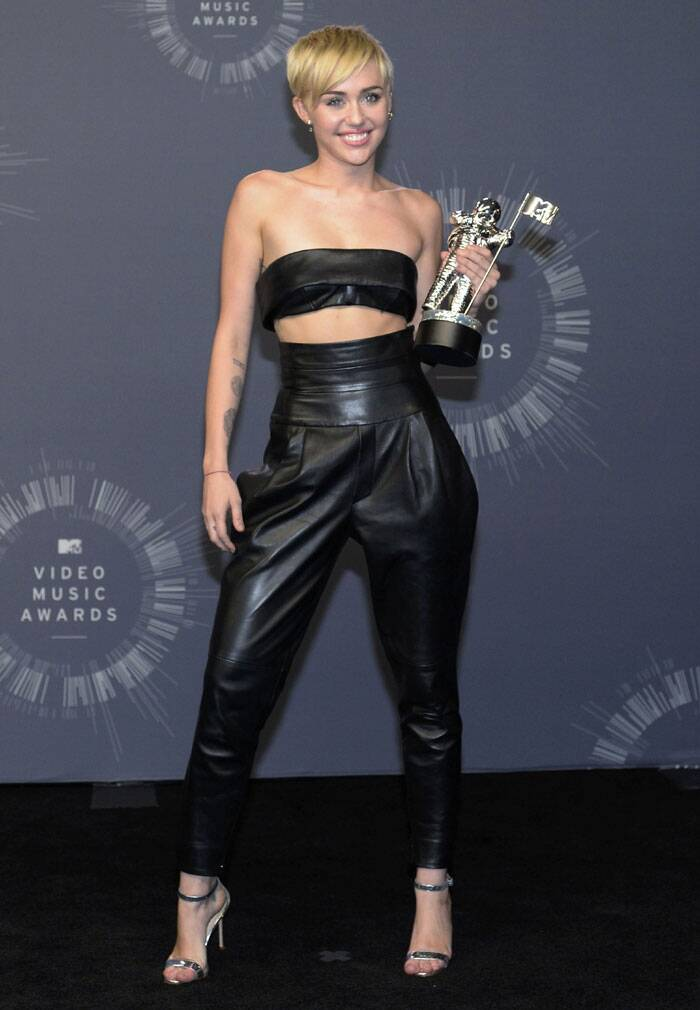 "Singer Miley Cyrus poses backstage after winning Video of the Year for ""Wrecking Ball"" during the 2014 MTV Video Music Awards in Inglewood, California. (Source: Reuters)"