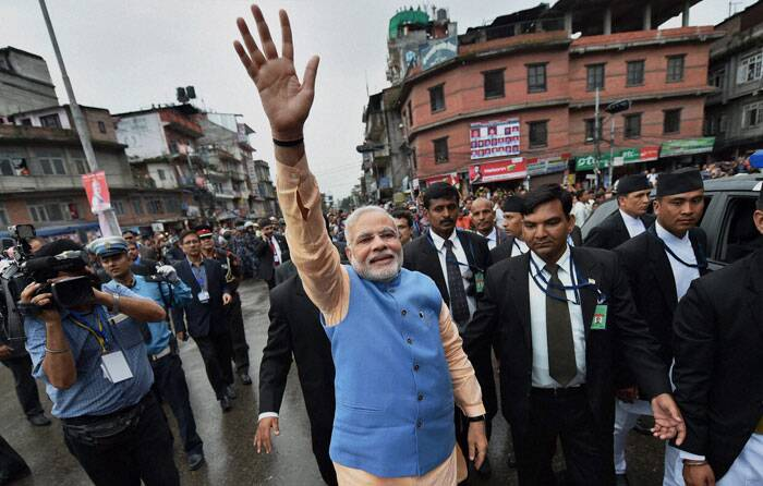 In a spontaneous gesture, Prime Minister Narendra Modi alighted to acknowledge thousands of people who lined up on the streets to greet him en route to the Parliament, in Kathmandu, Nepal on Sunday. (Source: PTI)