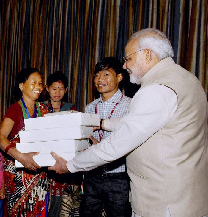 Narendra Modi giving presents to the family of Jeet Bahadur (2R) in Kathmandu, Nepal. The young boy has been raised by the PM in Gujarat, India. (Source: PTI)