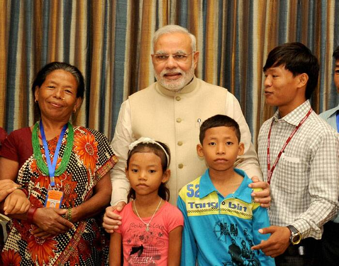 Prime Minister Narendra Modi with the family of Jeet Bahadur (R) in Kathmandu, Nepal on Sunday. The young boy has been raised by the PM in Gujarat. (Source: PTI)