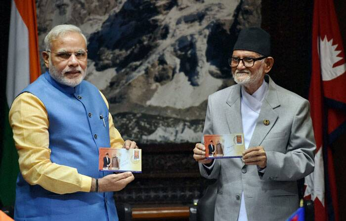 Prime Minister Narendra Modi and Nepal's Prime Minister Sushil Koirala showing the postage stamp during the signing ceremony at Chambers PMO, Singha Durbar in Kathmandhu Nepal on Sunday.  (Source: PTI)