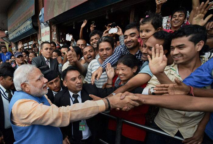 Prime Minister Narendra Modi meeting people lined up on the roads, on his way back after addressing the Nepalese Parliament in Kathmandu, Nepal on Sunday. (Source: PTI)