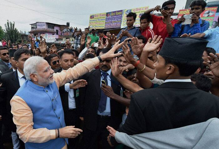 Prime Minister Narendra Modi greets thousands of people lined up on the streets while returning back from the Nepalese Parliament in Kathmandu, Nepal on Sunday. (Source: PTI)