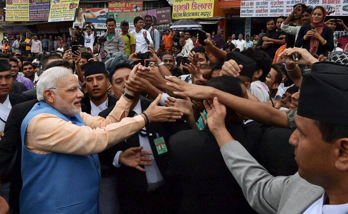 Narendra Modi greets people on the streets on his way back to the hotel after addressing the Nepalese Parliament in Kathmandu, Nepal on Sunday. PTI