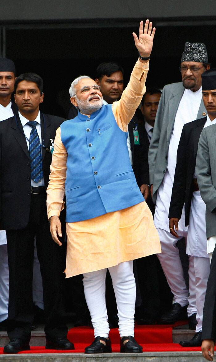 Prime Minister Narendra Modi waves to the media as he comes out after a meeting with his Nepalese counterpart Sushil Koirala, at the prime minister's office in Katmandu, Nepal on Sunday. (Source: PTI)