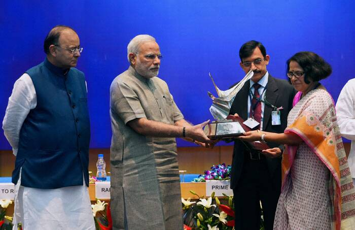 """We can be the world leader by not following but by showing the way,"" the Prime Minister said at a function organised here to give away DRDO awards. <br /> Prime Minister Narendra Modi along with Defence and Finance Minister Arun Jaitley, presenting the Titanium trophy to the Defence Institute of Physiology and Allied Sciences (DIPAS) at the DRDO Awards 2013 function in New Delhi. (Source: PTI)"