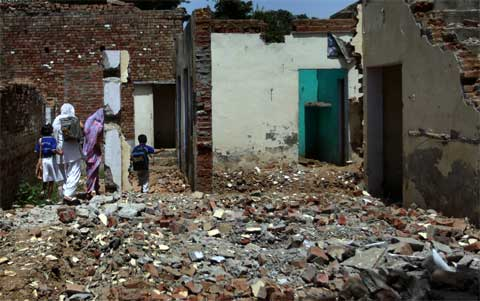 Village kids pass through houses that were abandoned during the Muzaffarnagar riots in Kakra Village. Most of the houses owned by the other community in the village  are on sale or have been sold. (Source: Express photo by Oinam Anand)