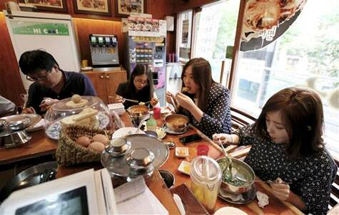 "In this Aug. 19. 2014, customers eat ""ramyeon"" instant noodle at a ramyeon restaurant in Seoul, South Korea. (Source: AP)"