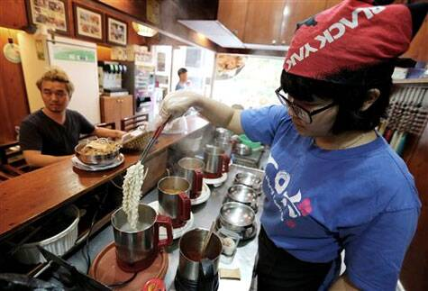 "In this Aug. 19. 2014 photo, a cook prepares ""ramyeon"" instant noodles for Han Seung-youn, left, during an interview at a ramyeon restaurant in Seoul, South Korea (Source: AP)"