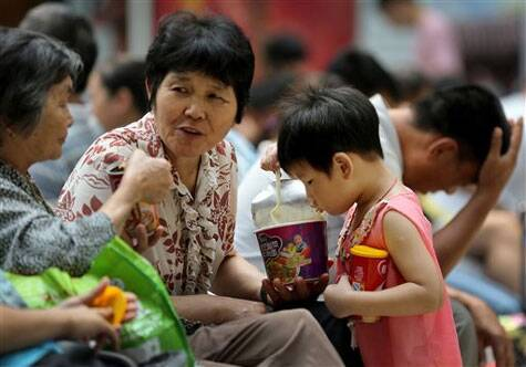 In this Sunday, Aug. 17, 2014 photo, a child eats instant noodle at a train station in Beijing. (Source: AP)