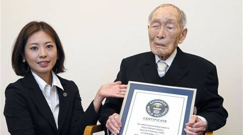 Sakari Momoi, a 111-year-old Japanese retired educator, poses for a photo after receiving a certificate from a Guinness World Records official, left, in Tokyo, Wednesday.