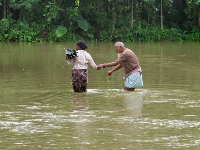 Officials said floods have also damaged standing crops in 112,635.25 hectares of land. The National Disaster Response Force (NDRF) and the State Disaster Response Force (SDRF) have been pressed into service.<br /><br /> An elderly couple struggles to make their way through flood waters at Dhupguri in Jalpaiguri district on Tuesday.  (Source: PTI Photo)