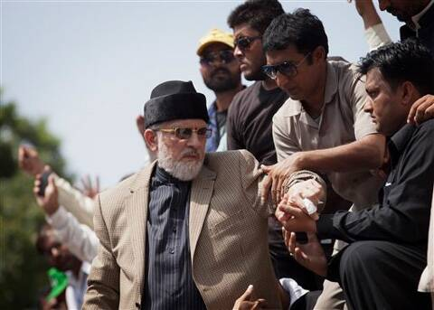 People help the anti-government cleric Tahir-ul-Qadri to get down from a stage at a public rally in Islamabad, Pakistan. (Source: AP photo)