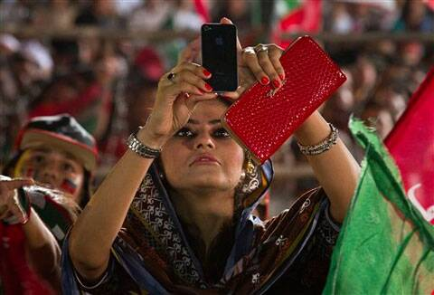 A supporter of Pakistan's cricketer-turned-politician Imran Khan uses her cell phone to take picture of Khan during a protest near the parliament building in Islamabad. (Source: AP photo)