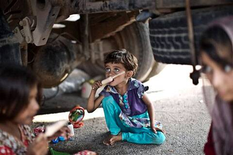 Children who have accompanied their families to a protest in front of the Parliament building shelter from the sun under a truck eating ice cream, in Islamabad. (Source: AP photo)