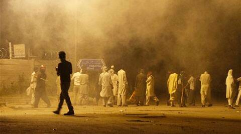 Pakistani protesters gather at a road while police fire tear gas shell to disperse them during clashes in Islamabad, Pakistan, Sunday, Aug. 31, 2014. ( Source: AP )