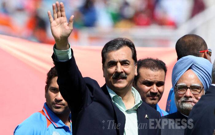 Pakistan PM Yousuf Raza Gilani and former PM Manmohan Singh wave even as cricketer Sachin Tendulkar looks on during the World Cup semi-final match between India and Pakistan, in Mohali. (Source: Express photo by Ravi Kanojia)