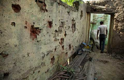 An Indian villager walks past marks on the wall of a house caused by mortar rounds fired from the Pakistan side of the border at Treva village in Arnia sector of J&K. (Source: AP)