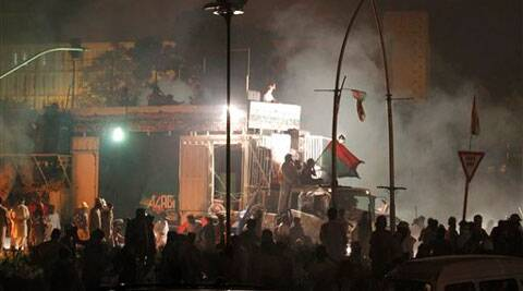 Pakistani protesters gather around a container which carries cricketer-turned-politician Imran Khan.