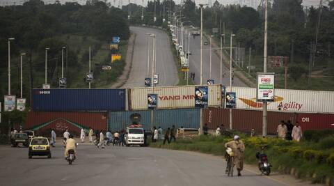 Ahead of planned massive anti-government protests, one of the roads to Islamabad is blocked by shipping containers in Islamabad, Pakistan. (Source: AP)