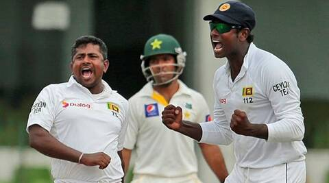 Sri Lanka's Angelo Matthews and Rangana Herath celebrates the fall of another Pakistan wicket on day two in Colombo. (Source: AP)