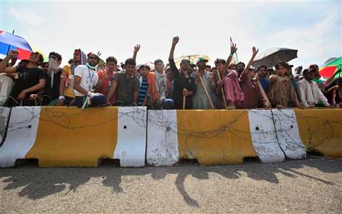 Jubilant anti-government demonstrators in Pakistan are claiming victory after tearing down barricades and occupying a key road outside Parliament. (Source: AP)
