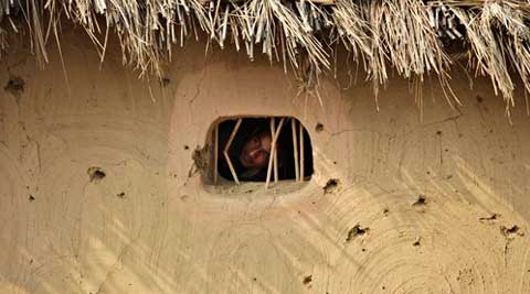A villager looks out a window of a hut damaged allegedly by gunfire from the Pakistan side of the border at Jora Farm village, in Ranbir Singh Pura region. (Source: AP)