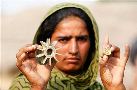 A woman displays a mortar shell allegedly fired on a residential area from the Pakistan side of the border in Ranbir Singh Pura region. (Source: AP Photo)