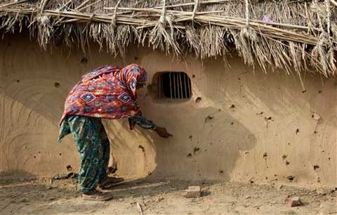A village woman points at holes made allegedly by gunfire from the Pakistan side of the border at Jora Farm village. (Source: AP)