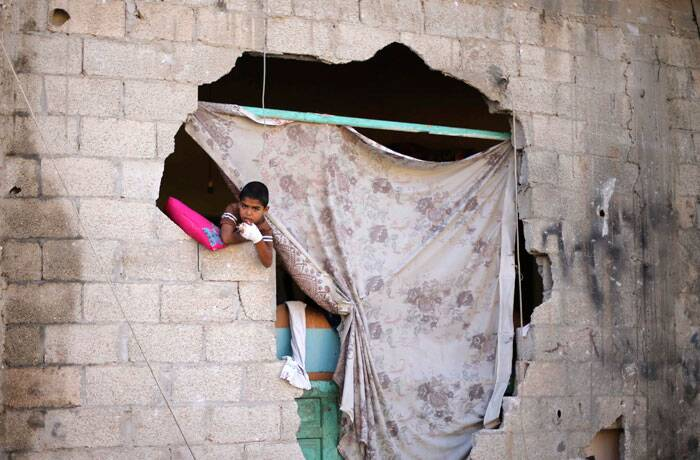 A Palestinian boy looks out of his damaged house after a ceasefire was declared, in the east of Khan Younis in the southern Gaza Strip August 27, 2014. The open-ended ceasefire in the Gaza war between Israel and the Palestinians held on Wednesday as Prime Minister Benjamin Netanyahu faced strong criticism in his country's newspapers over a campaign in which no clear victor emerged. (Source: Reuters)